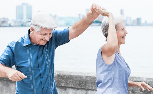 Starší muž a žena se baví venku u moře/pláže s městem/obzorem v pozadí