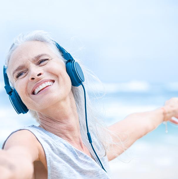 Žena v tílku se sluchátky na uších drží ruku. Je u moře / na pláži.